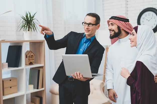 Makelaar toont binnenlandse arabische klanten kijken en glimlachen.