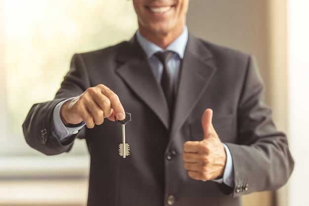 Makelaar van middelbare leeftijd die in klassiek kostuum een sleutel houdt