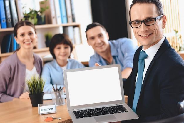 Makelaar zittend aan een bureau en de presentatie van de laptop.