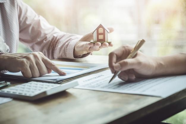 Makelaars in onroerend goed die discussiëren over leningen en rentetarieven voor het kopen van huizen