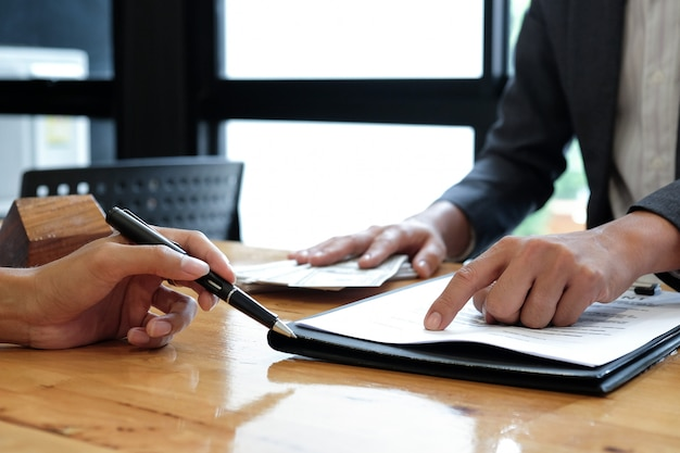 Makelaars in onroerend goed wezen op het ondertekenen van overeenkomstdocumenten.