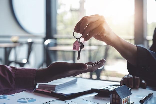 Makelaars komen overeen om een huis te kopen en sleutels te geven aan klanten op het kantoor van hun bureau.