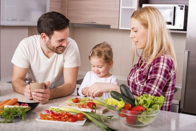 Maken van een salade met verse groenten op het aanrecht en gelukkige familie