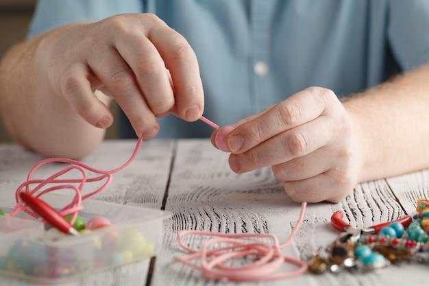 Maken van handgemaakte sieraden, vooraanzicht van mannelijke handen