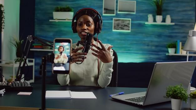 Maker van inhoud kijkt naar de camera van de smartphone terwijl hij aan de microfoon praat en controleert het geluid tijdens podcast