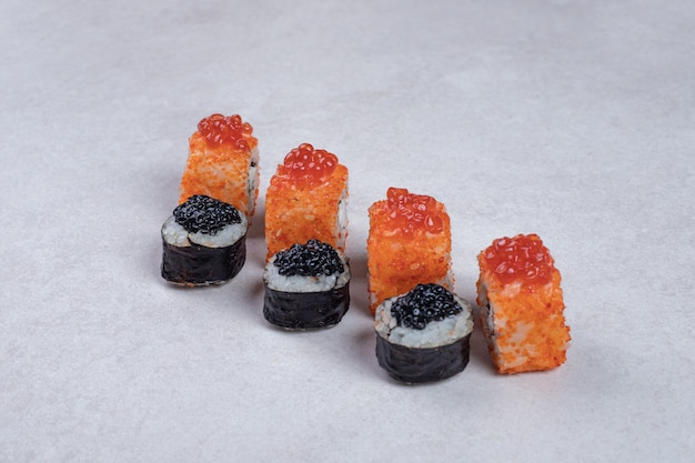 Maki en californië sushibroodjes op witte ondergrond.
