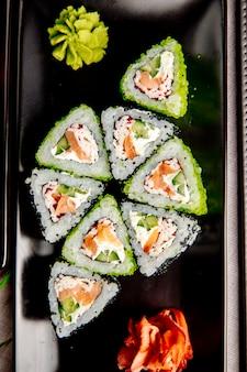 Maki met zalm en krabroom. kaas rijst komkommer gember wasabi bovenaanzicht