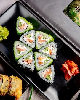 Maki met zalm en krabroom. kaas rijst komkommer gember wasabi zijaanzicht