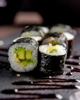 Maki roll met avocado geserveerd met saus