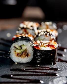Maki roll met komkommer geserveerd met saus en sesamzaadjes