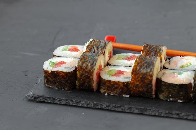 Maki sushi roll geserveerd op stenen plaat op grijs