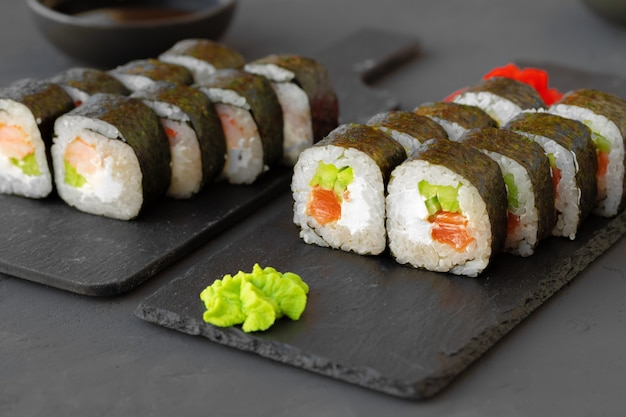 Maki sushi roll geserveerd op stenen plaat op grijze close-up