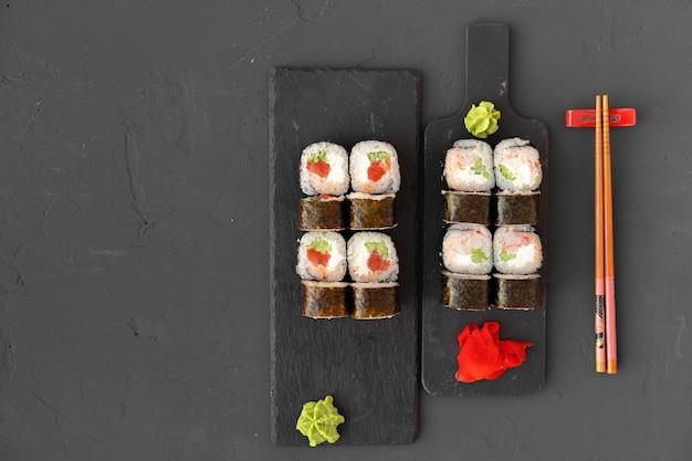 Maki sushi roll op zwarte stenen plaat bovenaanzicht