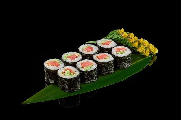 Maki sushi rolls met gerookte zalm en komkommers op bamboeblad