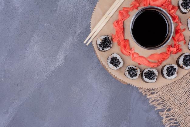 Maki sushi rolt op houten plaat met stokjes, ingelegde gember en sojasaus.
