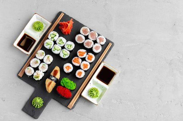 Maki sushi set geserveerd op zwarte stenen dienblad close-up