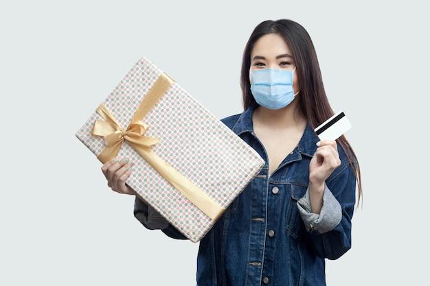 Makkelijk kopen met online shoppen. tevreden jonge aziatische vrouw met medisch masker in spijkerjasje dat aanwezig is en een bankkaart vasthoudt, kijkend naar de camera. geïsoleerd, studio-opname, grijze achtergrond