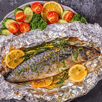 Makreel gebakken in folie met groenten op een schotel, bovenaanzicht