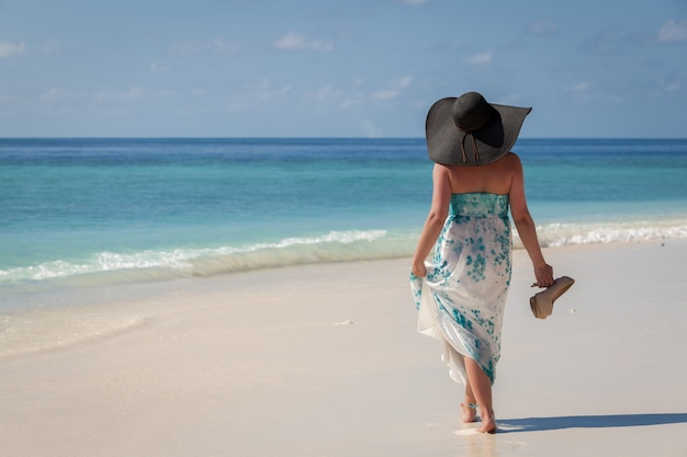 Maldiven, jonge vrouw wandelen langs het strand met zonnehoed en hoge hakken aan de kant