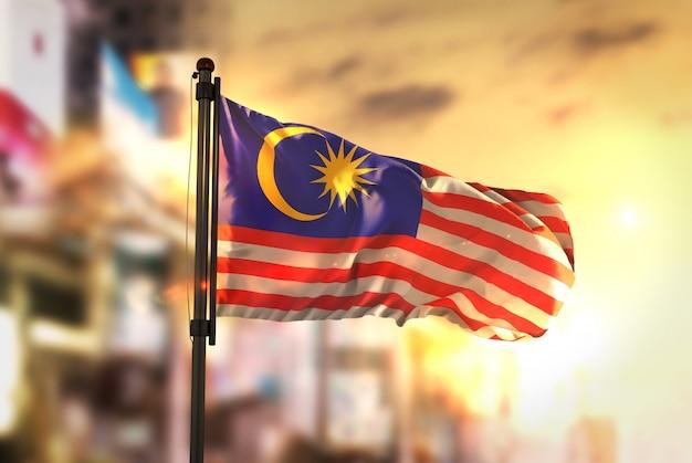 Maleisië vlag tegen stad wazige achtergrond bij zonsopgang achtergrondverlichting