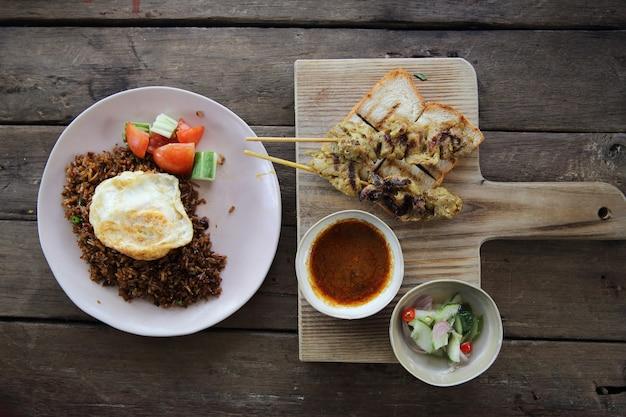 Maleisische kipsaté met pindasaus op houtachtergrond