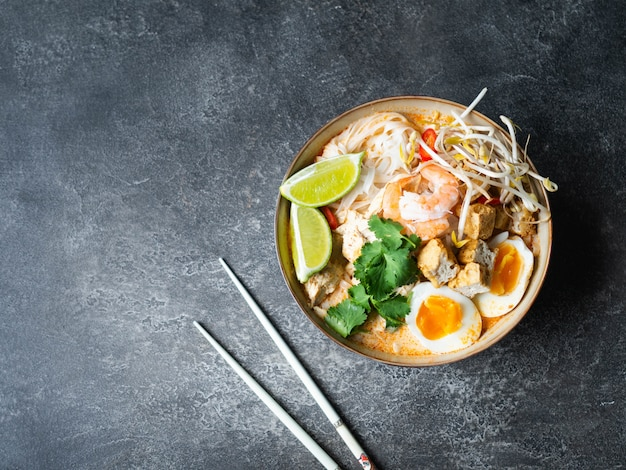 Maleisische noedelslaksa-soep met kip, garnalen en tofu in een kom op een donkere ondergrond