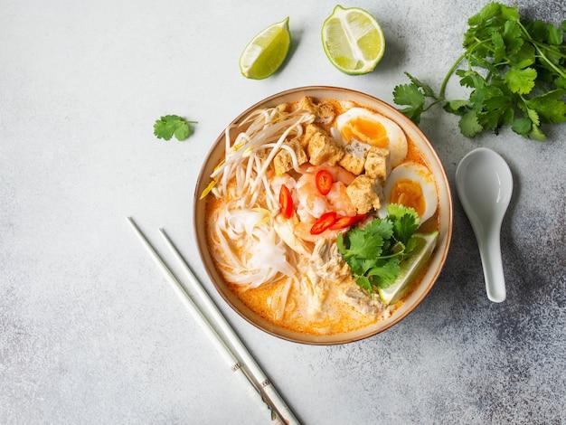 Maleisische noedelslaksa-soep met kip, garnalen en tofu in een kom op grijze oppervlakte