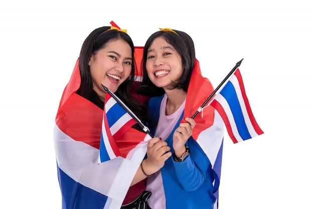 Maleisische vrouw die de nationale vlag van thailand houden