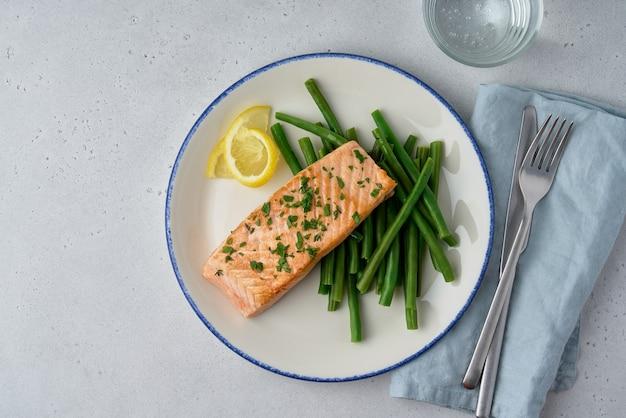 Mals en sappig gebakken zalmfilet met groenten gezonde gemakkelijke maaltijd overhead kopie ruimte