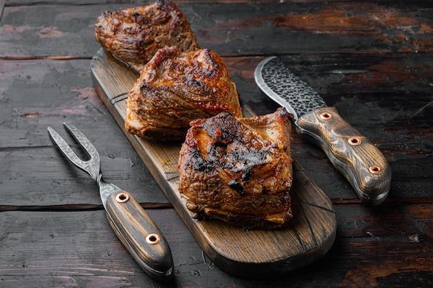 Mals gekookte ribben in een heerlijke, rijke sausreeks, op oude donkere houten lijstachtergrond