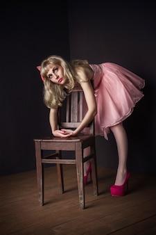 Malvina meisje in roze jurk liggend op de stoel