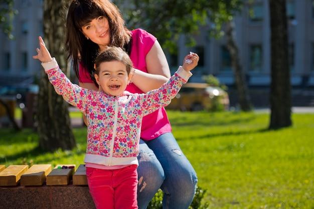 Mam doet een kapsel voor haar kleine charmante dochter in het park op een bankje