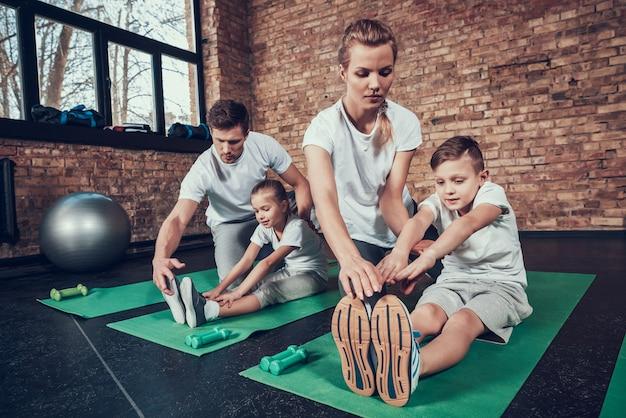 Mam en pap leren kinderen die zich uitstrekken in de sportschool