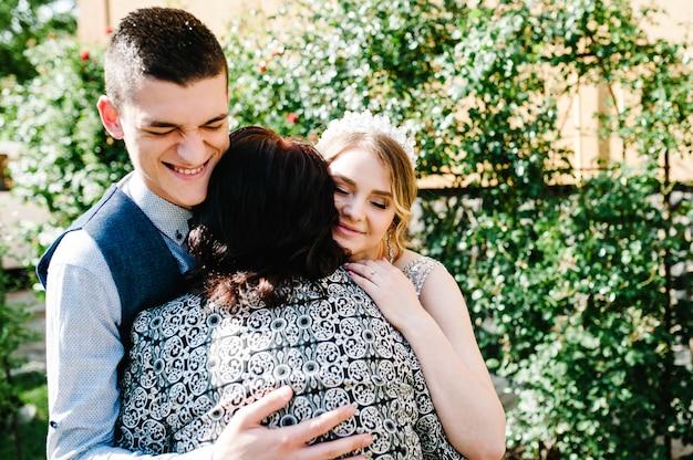 Mam feliciteert de bruiden met een huwelijk en knuffels. huwelijksceremonie.