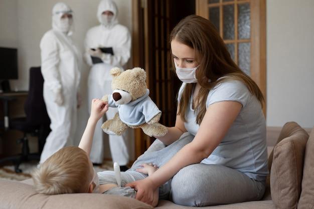 Mam meet de temperatuur van de baby. artsen in beschermende pakken bij zieke patiënten thuis. coronavirus (covid-19