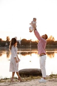 Mam, pap tilt zijn schattige babymeisje hoog op en kijkt haar glimlachend aan. gelukkige ouders tijd doorbrengen met spelen met dochter in park bij zonsondergang. medium schot. selectieve aandacht.