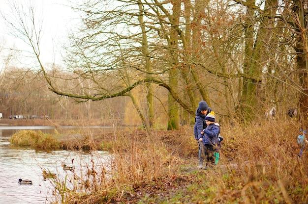 Mama en een kind die eenden voeren