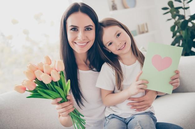 Mama en haar dochter zitten op de bank en houden een briefkaart van rozenboeket binnenshuis binnenshuis