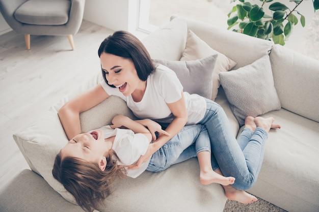 Mama en haar dochtertje spelen kietelen op divan in appartement binnenshuis