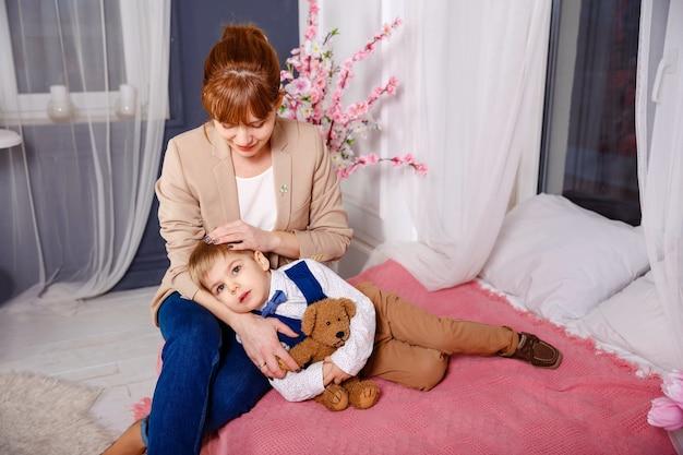 Mama en jongen lezen een boek in bed voordat ze gaan slapen. moeder legt haar zoon 's avonds in bed. kind slaapt in moeders armen. ze brengen elk mogelijk moment samen door. familie thuis.
