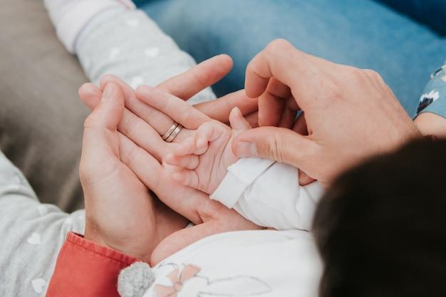 Mama en papa houden de hand van de baby vast. kinderhandvat