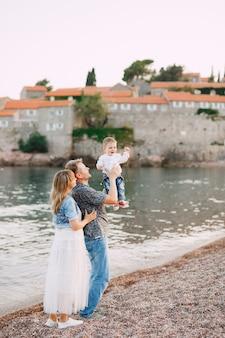 Mama en papa houden hun zoontje in hun armen aan zee tegen de achtergrond van het eiland sveti stefan