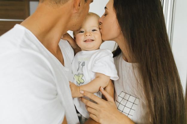 Mama en papa kussen hun zoontje. het kind verheugt zich.