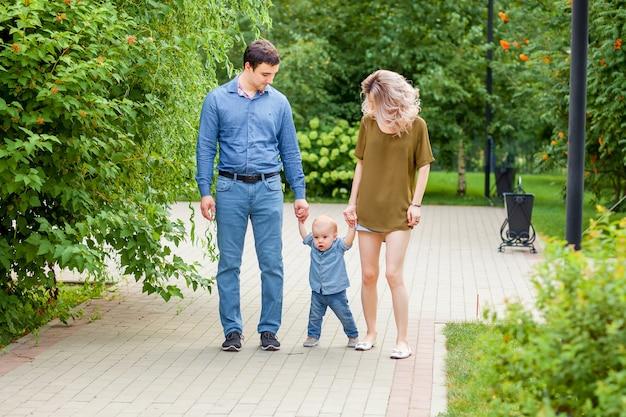 Mama en papa lopen met de baby in het park