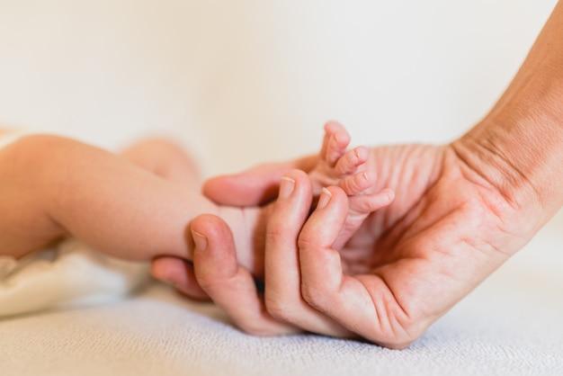 Mama grijpt de voetjes van haar pasgeboren dochter.