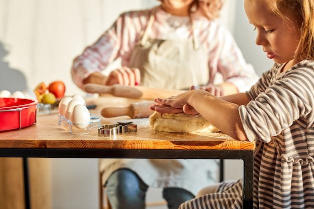 Mama helpt kind dochter rollend deeg voor zelfgemaakte koekjes of taart. twee vrouwelijke generaties familie genieten van kookproces samen in de keuken, in huiselijke sfeer