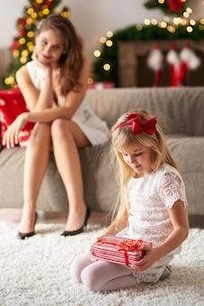 Mama kijkt naar dochter terwijl ze cadeautjes opent