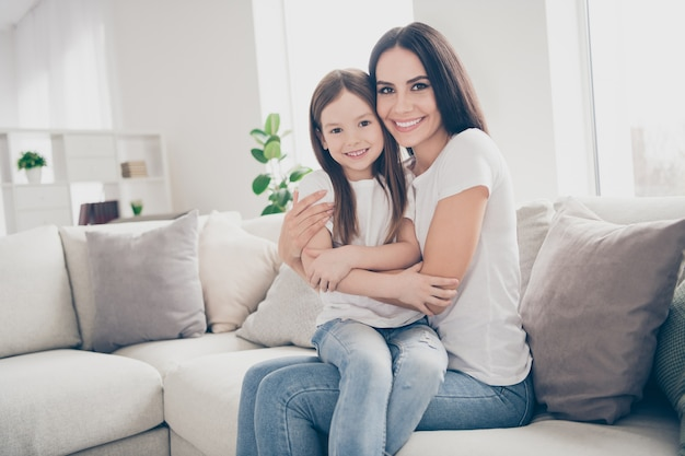 Mama knuffelen haar dochtertje in huis