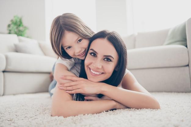Mama knuffelt haar kind-meisje op tapijt in het lichte appartement van de kamer