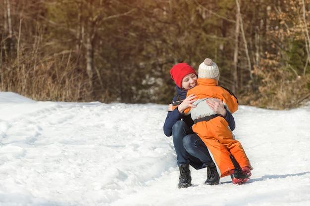 Mama omhelst de kleine zoon op een achtergrond van dennenbos. winter besneeuwde dag in het naaldbos